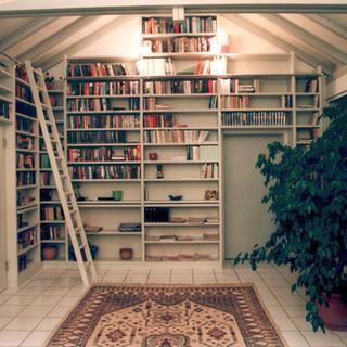 weiß lackierte Bibliothek in Dachschräge mit Leiter auf einer Schiene
