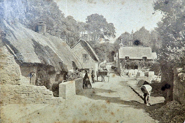 Looking towards the Old Smugglers Cottage, Shepherds Lane (now Village Road). Ellen Sewell is pictured entering the house and Mr Woodford the stonemason is to the right in the foreground. With thanks to Andy Butler