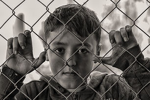 Canva - Young Boy Looking through a Fenc