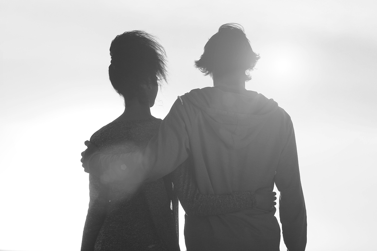 young-couple-embracing-looking-at-sunset