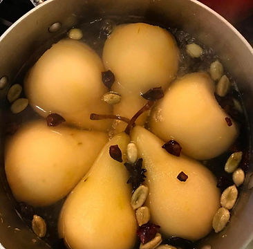 Pears poaching in a pot with cinnamon, cardamom and star anise