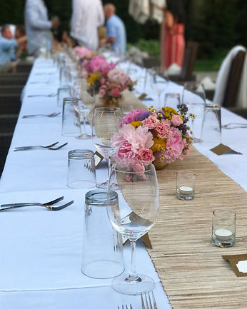 A long table sumptuously set for an outdoor meal