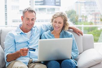Imagem de um casal de meia idade segurando um cartão de crédito sentados no sofá da varanda.