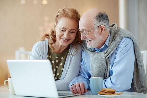 Imagem de um casal de meia idade sorrindo e sentados em uma mesa olhando um notebook