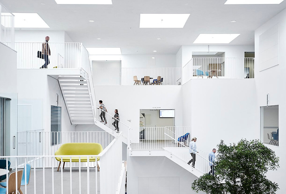 Átrio de escola com escadas e sacadas. Tratamento lumínico e acústico.