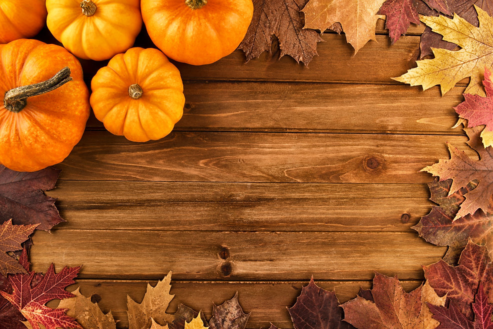 Pumpkins with fall leaves over wooden ba