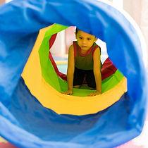 Criança engatinhando num túnel feito de tecido.