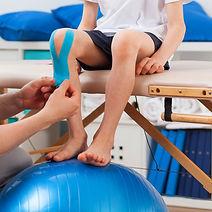 Terapeuta aplicando bandagem elástica no joelho de uma criança.