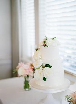 white wedding cake, fresh flowers