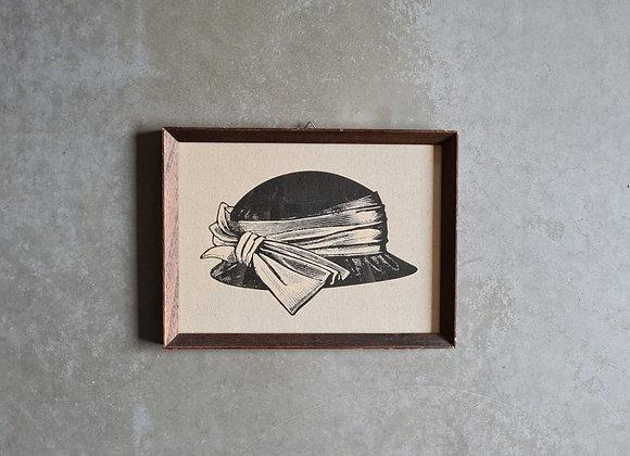 'תמונה של כובע נשים במסגרת וינטג