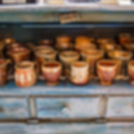 Wood fired pottery cups in a rustic blue cabinet.