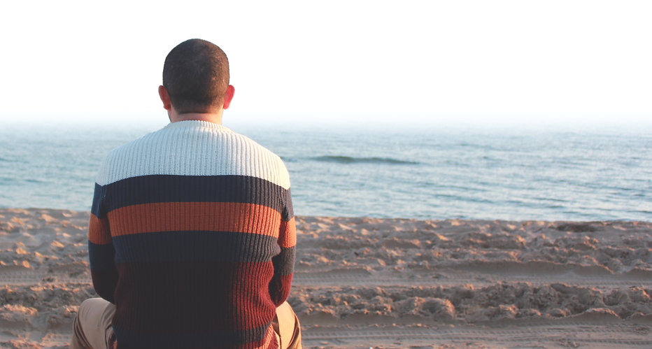 Man staring out to the sea, reflecting on life after therapy session
