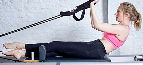 4U Pilates member in a Reformer Pilates class demonstrating a movement on the reformer machine