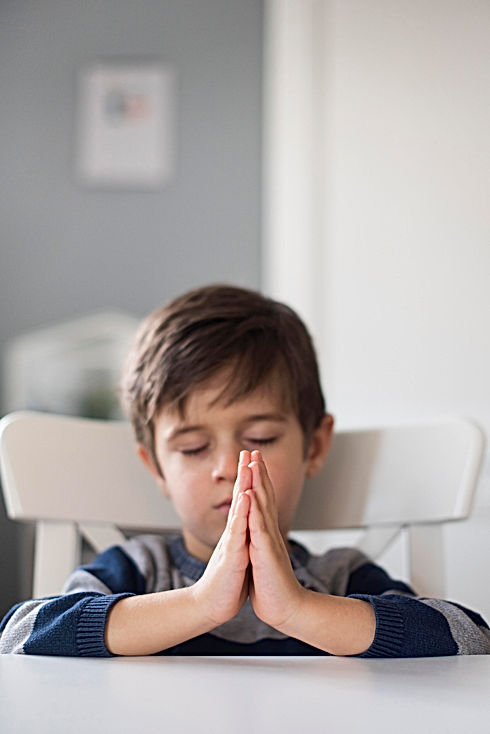 portrait-of-young-boy-praying-at-home.jp