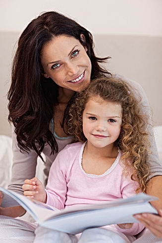 smiling-mother-reading-bedtime-story-wit
