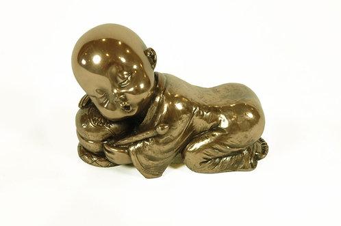 Figura de niño monje descansando.