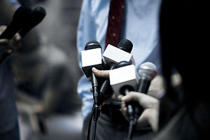 News image of people holding out microphones