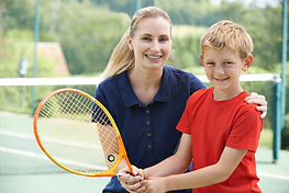 Junge mit Tennis-Trainer