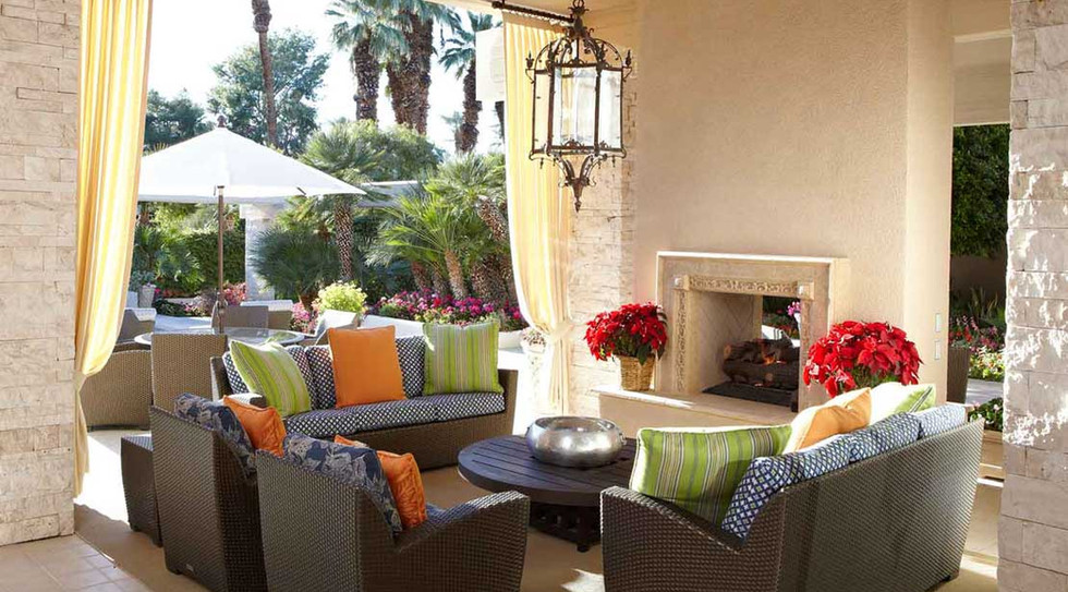 Covered, terrace entertainment area with friendly colors and beautiful fireplace