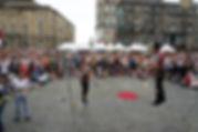 מופע קרקס רחוב בפסטיבל אדינבורג עם הליכה על חבל ולהטוטנות אש. מופע של קרקס און אוף