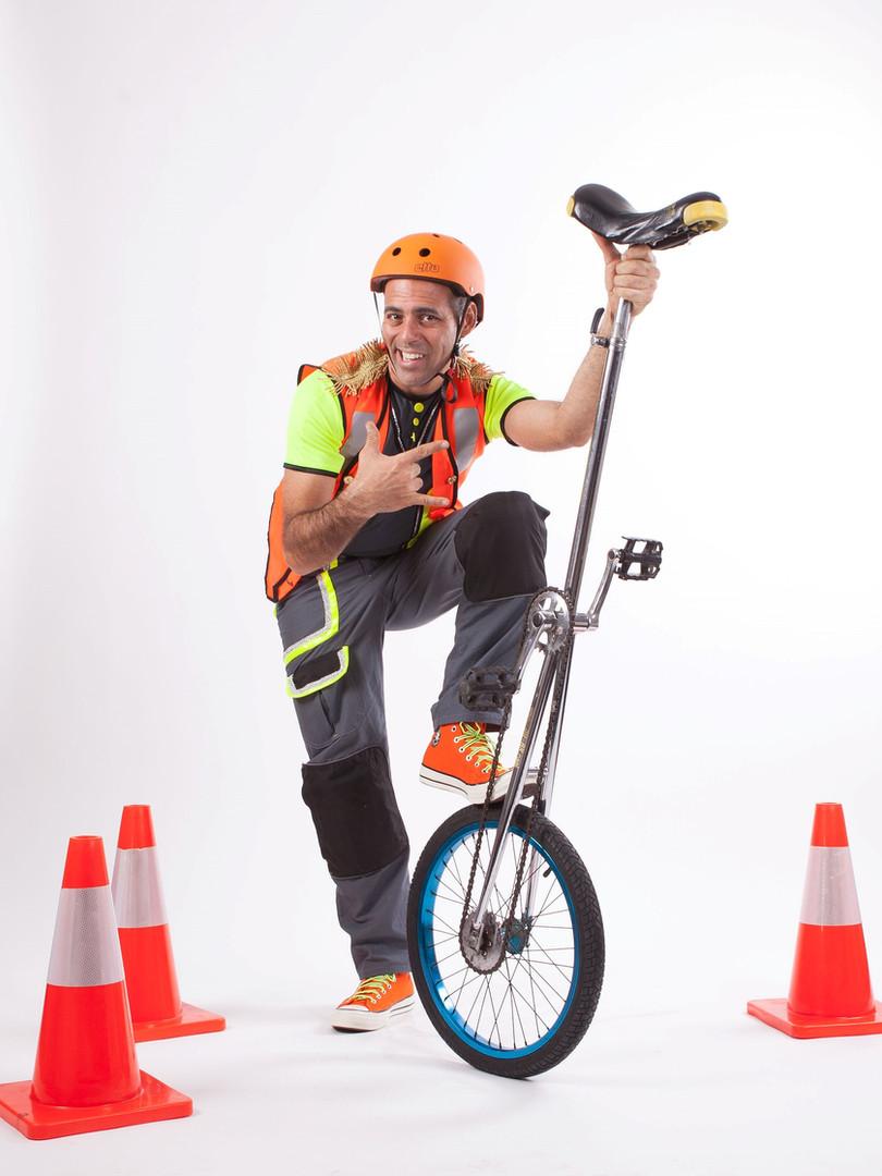 איש עם חד אופן גבוה במופע קרקס זהירות בדרכים