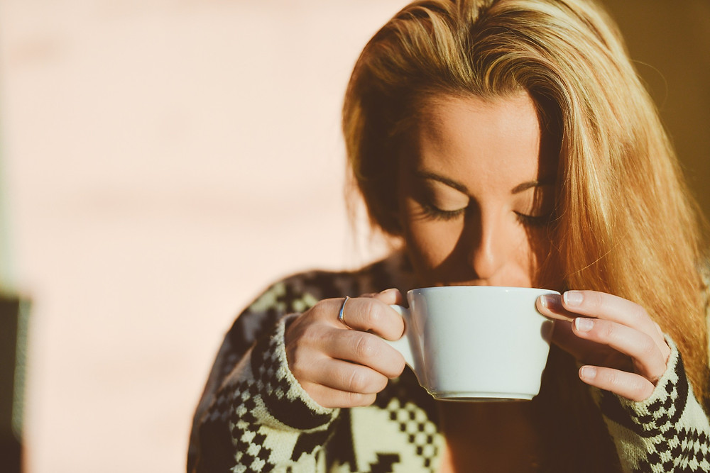 a woman drinking tea for digestive and hormonal health