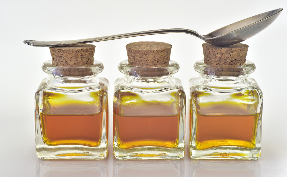 Jars of natural extract with spoon resting on top.