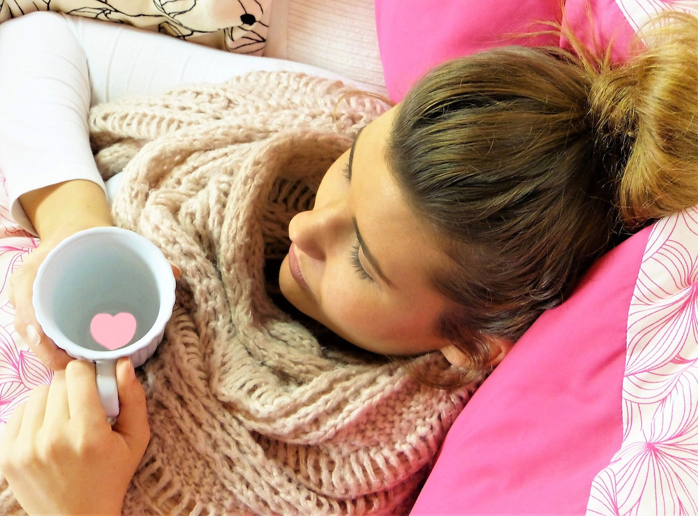 a woman laying down with a cup of tea, The Connection Between Epstein-Barr Virus (EBV) and Hashimoto's Thyroiditis