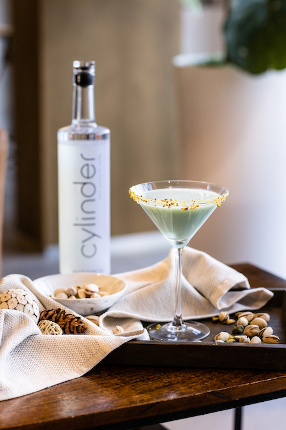 Cylinder Pistachio Martini on a tray with pistachios