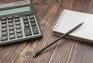 notebook-calculator-wooden-table_73102-1