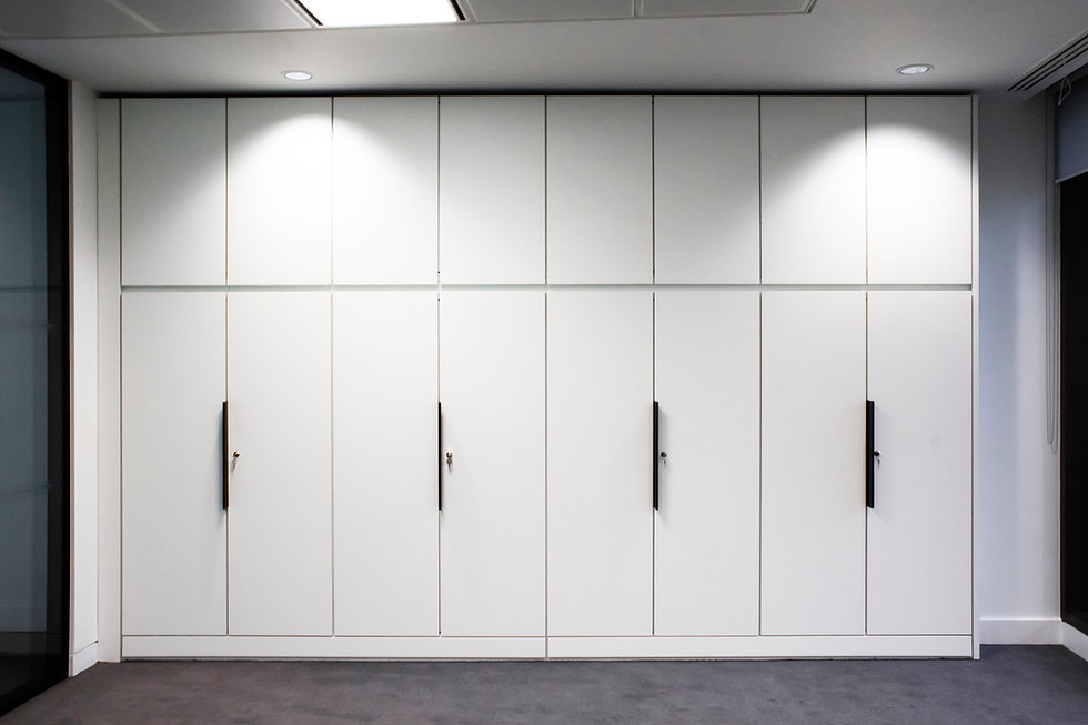 A run of Freewall's split level storagewall, finished in white MFC, installed in an office space. The bottom doors have a rosette lock and a large black trim handle. The upper doors have no handle, but a rebated strip runs underneath them, acting as a handle.
