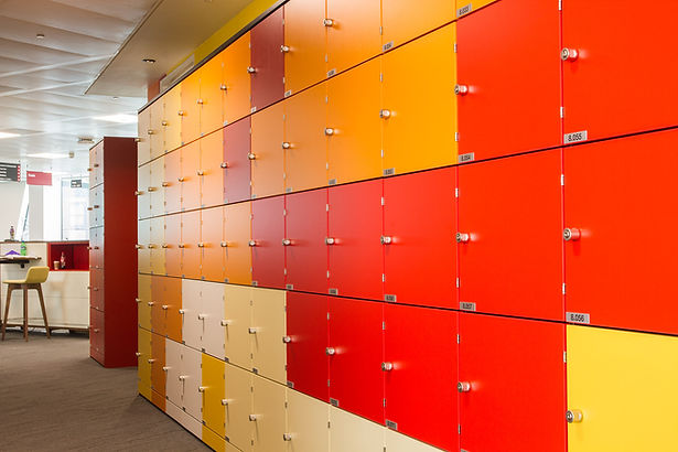 An array of locker doors finished in reds and oranges run down the length of an office wall. These Freewall storagewall lockers are capped, fitted with lockable turn handles and individually numbered.