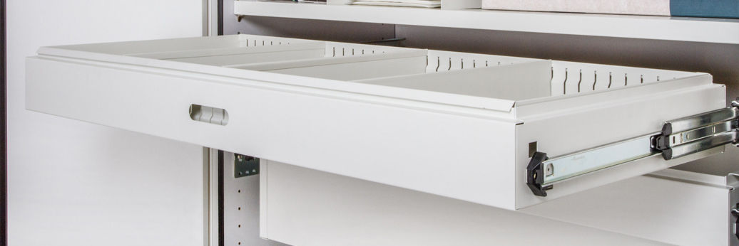 A shallow drawer insert fitted into a  roll out  filing frame. The drawer insert is fitted with several steel dividers