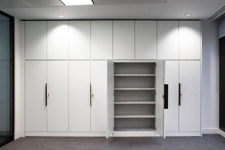 Run of split level storagewall, one of the bottom doors is open revealing the shelves inside the cupboard