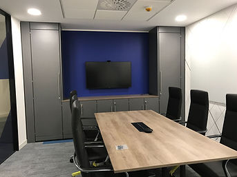 Freewall storagewall is being used to frame a TV in a boradroom. There are low-level units below the TV and full height units each side. The storagewall is finished in a dark grey, and fitted with long bar handles.