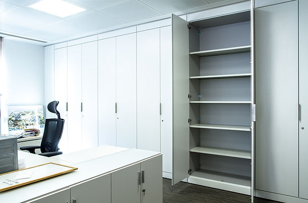 A run of Freewall storagewall fill the end of a personal office. These storage units are finished in white, with custom rosette locks and trim handles. one of the storagewall units is open, revealing the adjustable steel shelves inside.