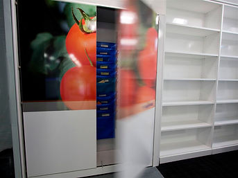 Freewall storagewall installed in a display area, units to the right are designed to be bookshelves, open faced and accessible. The units on the right have doors to concealed storage, but a large manifestation graphic on the front to brighten them up.