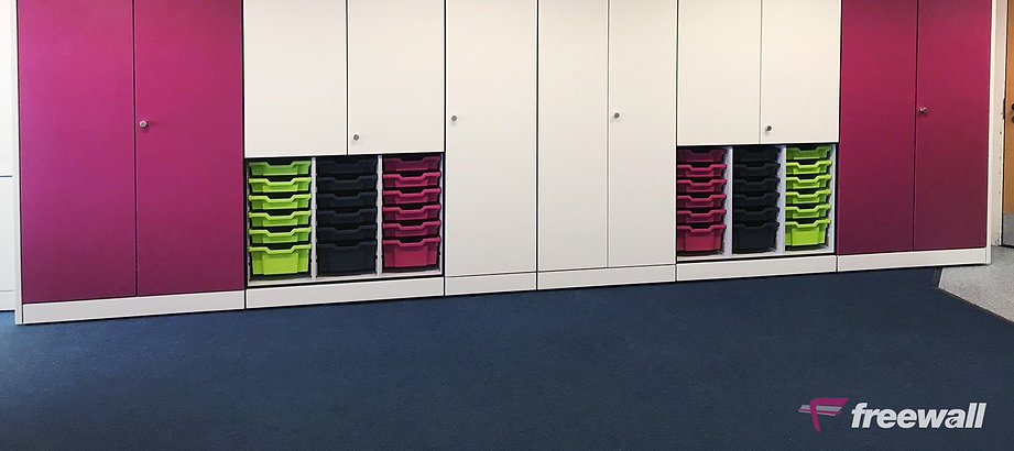 A run of Freewall Teacherwall Storagewall. This run has been designed mainly for general storage, it is fitted with full height doors, some finished in fucia pink. The lower sections of some of the units are open, with Gratnell trays accessible.