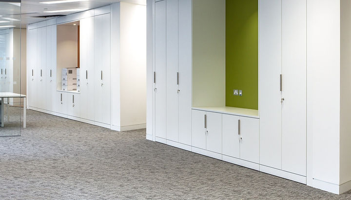 Freewall storagewall and alcove units along an office wall. The backs of the alcoves are painted green. The storagewall is fitted with special trim handles.