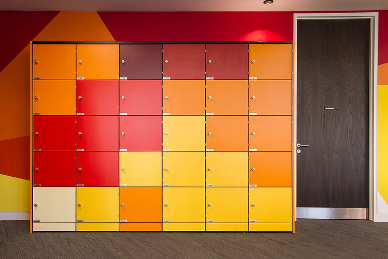A run of Freewall lockers in an office space. The lockers are finished in a range of yellow, orange and red MFCs.