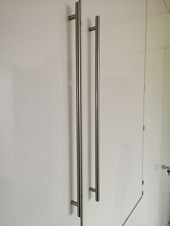Long steel bar handles fitted into storagewall