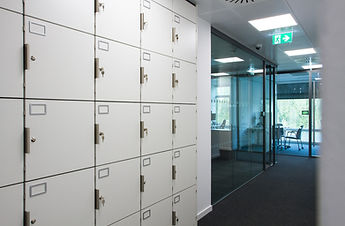 Freewall lockers installed in the corridor of an office. The lockers have custom handles fitted, and label holders for more personalised storage.