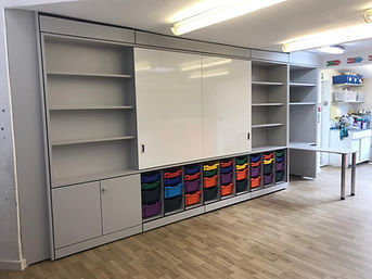 Freewall Teacherwall installed in a classroom. There are a range of units and features, including: sliding doors, upper alcoves with shelves, an integrated desk and Gratnel Tray storage.