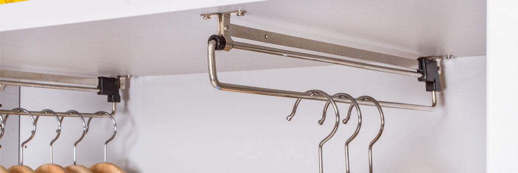 Pull out garment rails are fitted into the bottom of an MFC shelf in a storagewall unit. Coat hangers are suspended from the underside.