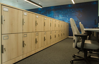 A row of Freewall lockers behind some hot desks. The units are finished in a maple wood, with custom handles and label holders