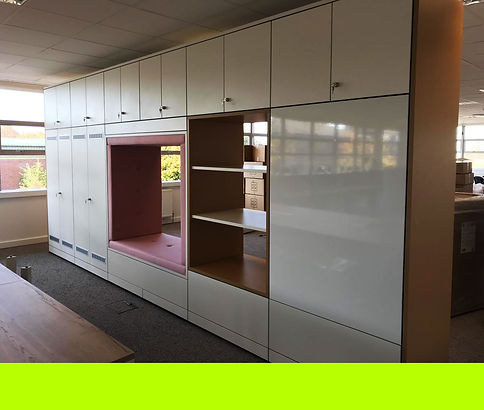 Run of Freewall storagewall in an office space. The storagewall is broken up into various unit types, including general storage with fitted vents, double sided alcoves, and a double sided seating alcove Cosywall unit. All fitted with lockable upper storage.
