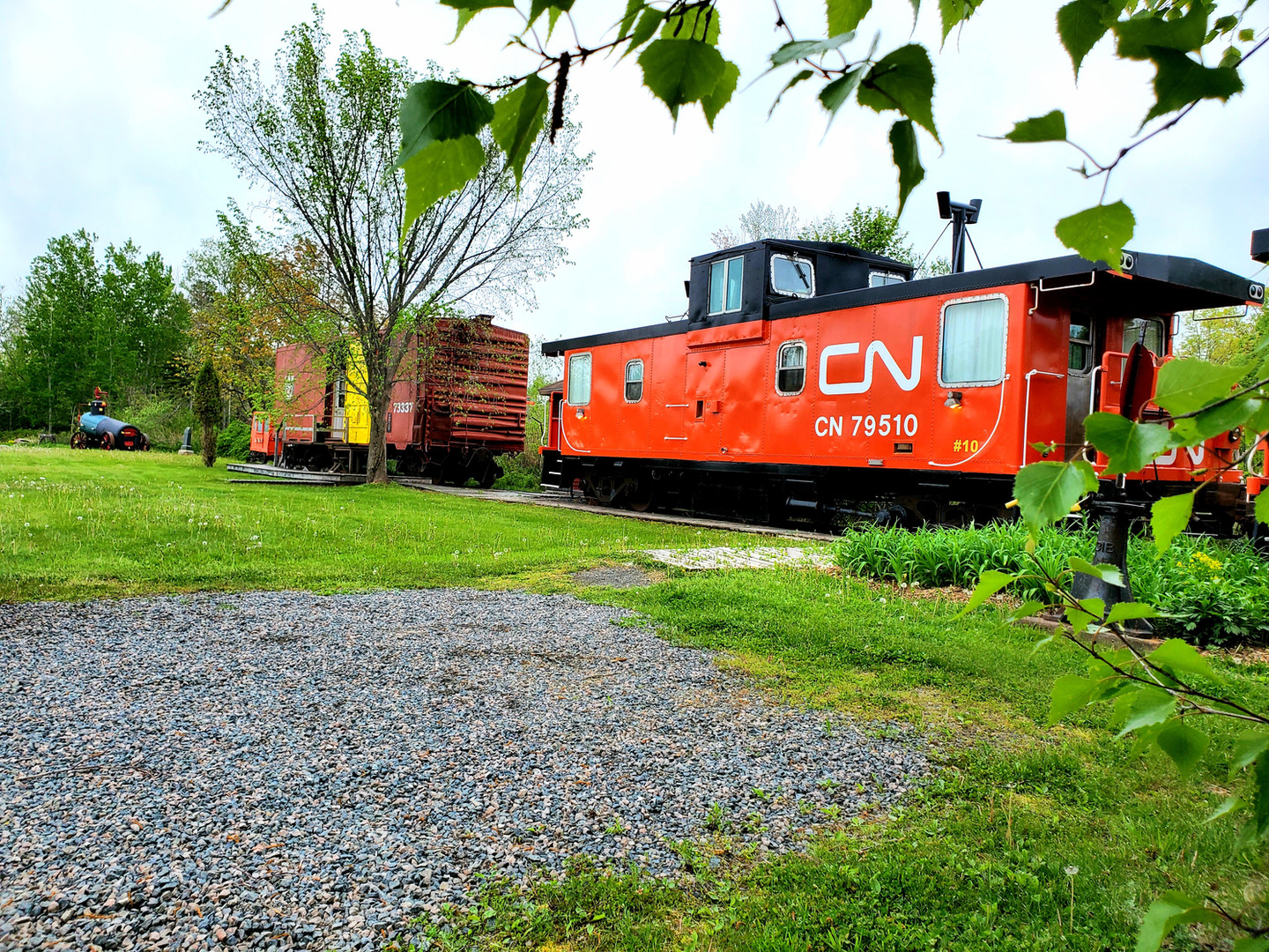 """Caboose 10 rests on the siding next to boxcar """"Jane""""."""
