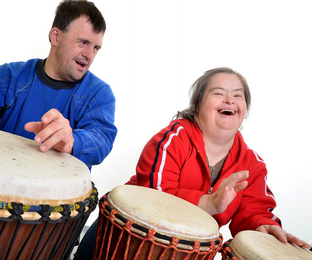 Adults with developmental disabilities laughing while playing the drums