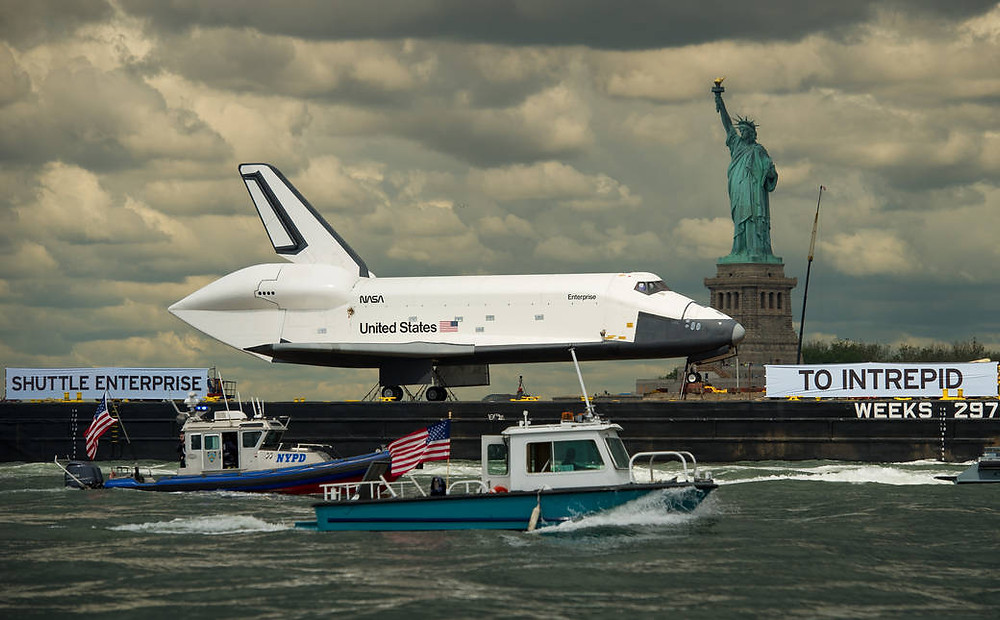 Space Shuttle Enterprise passing the Statue of Liberty