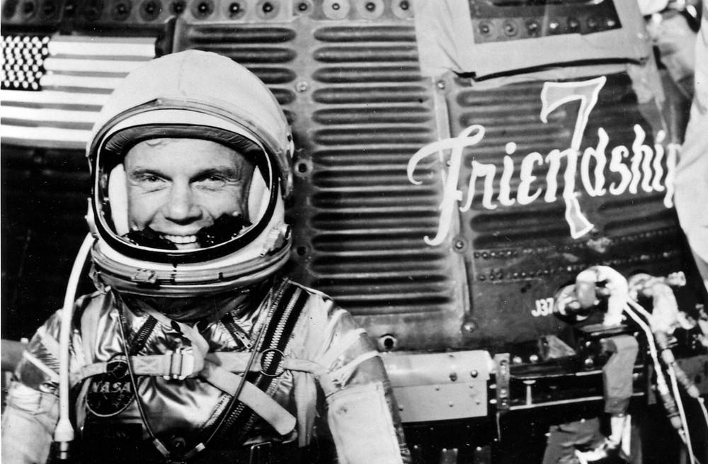 John Glenn posing with his Friendship 7 spacecraft before the launch of Mercury-Atlas 6